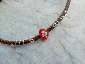 Leren halsketting choker met een oranje rode glaskraal. Versierd met verzilverd draad.